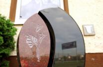 Zweiteiliger Formstein aus scharzem und rotem Material mit vertieft plastischer Calla